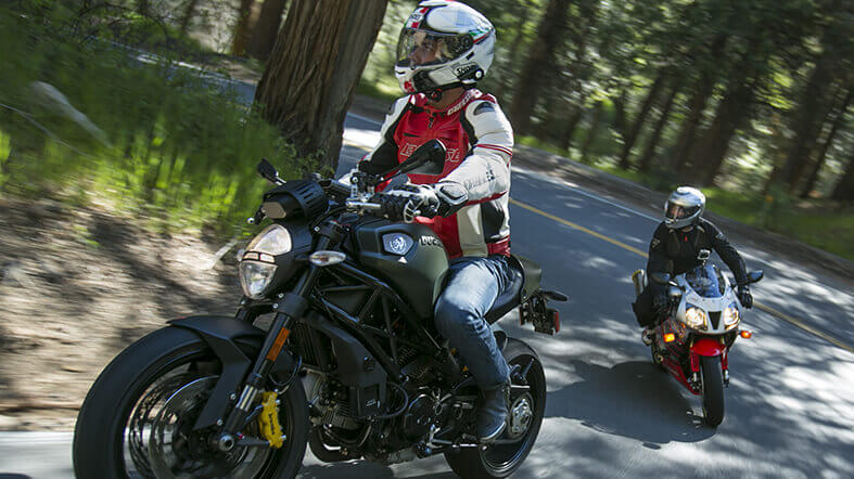 Two motorcyclists adventuring in the woods